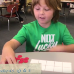 A Kindergarten student demonstrates addition and subtraction with objects