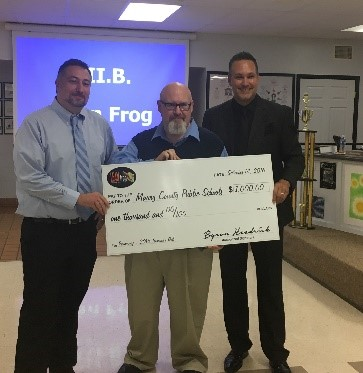 Board Chair David Bates and Superintendent Dr. Chris Marczak accept $1000 cash prize from LEAN Frog co-founder Byron Headrick